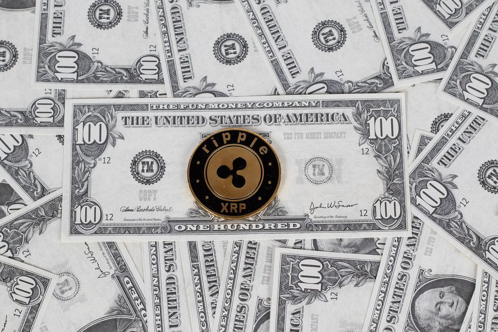 """""""Ripple coin on a paper dollars money""""bymarcoverch (licensed underCC BY 2.0)"""
