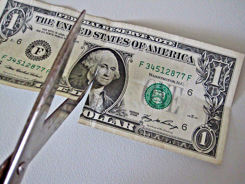 """""""$1 bill Cut by Scissors"""" by Images_of_Money is licensed under CC BY 2.0"""