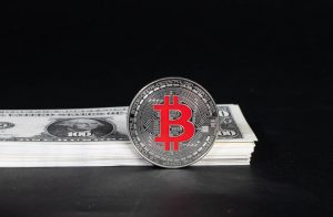 """""""Silver Bitcoin with stack of money"""" by marcoverch is licensed under CC BY 2.0"""